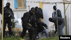 Forca te maskuara policore p⌂rcjellin një pjesëtar të komunitetit islamik nën masa të rrepta sigurie në Koueron, 3 0mars 2012