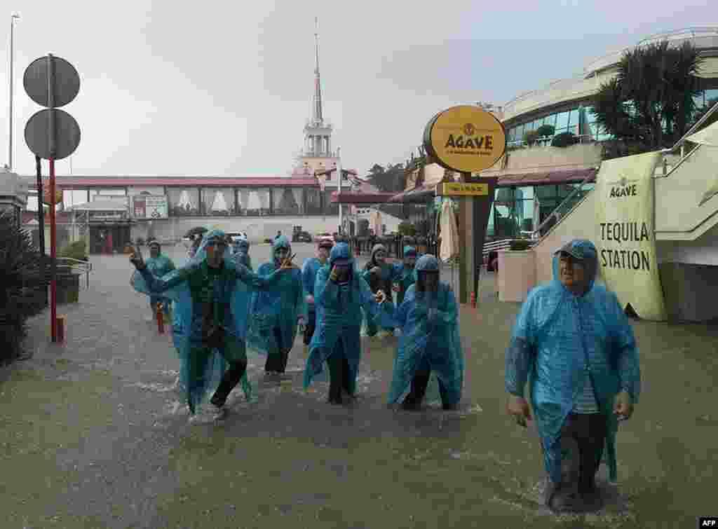 Люди в дождевиках идут по набережной Черного моря в Сочи