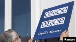 Belarus -- An OSCE employee removes signage from the OSCE office in Minsk, 29Mar2011