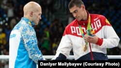 Russian boxer Yevgeny Tishchenko (right) shakes hands with Kazakhstan's Vasly Levit after their controversial heavyweight bout at the Rio Olympics.