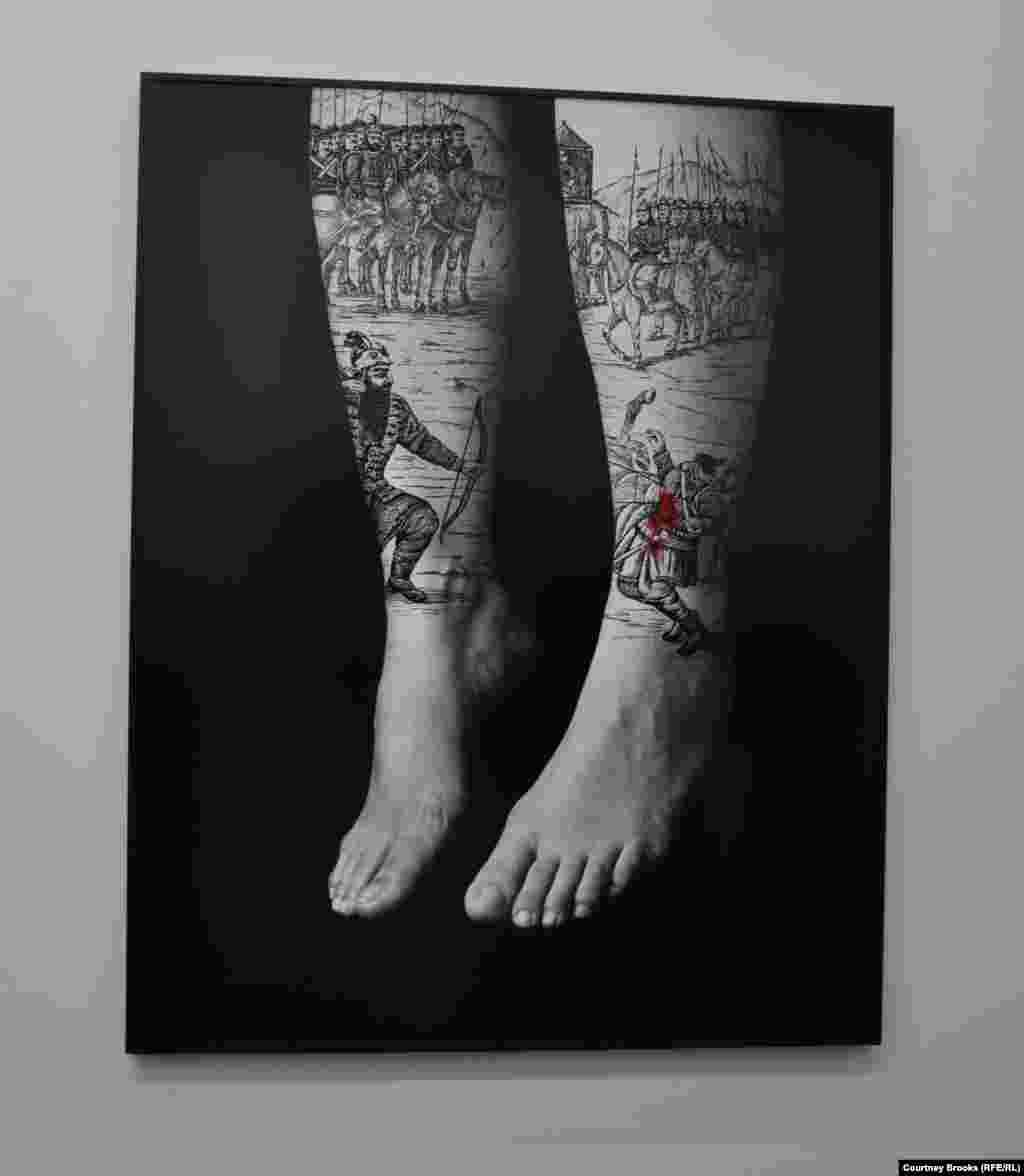 A photograph of hanging feet covered with battle scenes at Shirin Neshat's exhibition.