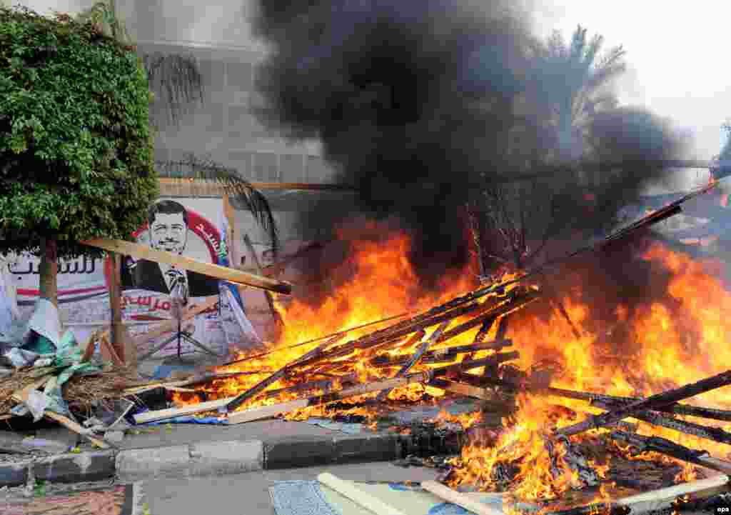 A tent burns as security forces clear the camp.