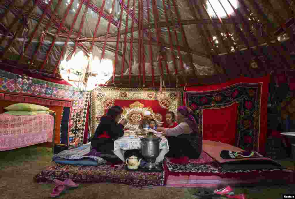 A family shares breakfast inside their yurt.