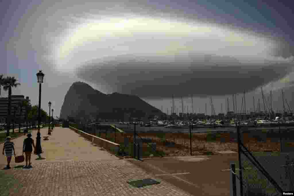 People walk along a street in front of the Rock of the British territory of Gibraltar (rear), a monolithic limestone promontory, next to the border in La Linea de la Concepcion, southern Spain. (Reuters/Jon Nazca)