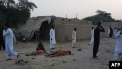 Pakistani devotees gather around the bodies of blast victims after a suicide bombing near a Sufi shrine in the Jhal Magsi district on October 5.