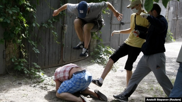 Gay-rights activist Svyatoslav Sheremet (on ground) is attacked during a May rally in Kyiv.