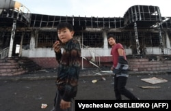 Масанчи ауылында өртенген ғимараттың қасынан өтіп бара жатқан балалар. Жамбыл облысы, 8 ақпан 2020 жыл.