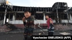 Молодые люди на фоне сгоревшего здания в селе Масанчи. 8 февраля 2020 года.