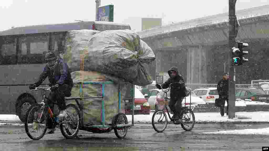 People ride bicycles during a snowfall in downtown Skopje, Macedonia.