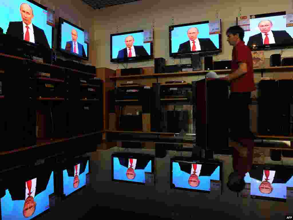 A shop assistant walks past TV screens during the broadcast of Russian Prime Minister Vladimir Putin's annual TV  marathon question-and-answer show  at a shop in a Moscow on December 16. Photo by Natalia Kolesnikova for AFP