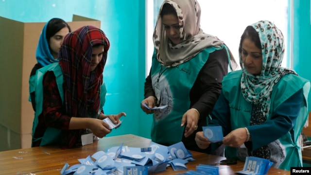 Afghan election officials count ballot papers after polls closed in Kabul on June 14.