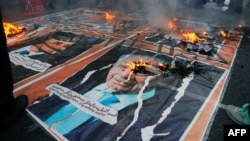 Iranians burn posters of U.S. and Israeli political figures, including the late Israeli President Shimon Peres, outside the former U.S. Embassy in Tehran on November 3.