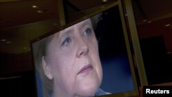 German Chancellor Angela Merkel is seen on a TV monitor as she prepares to record her annual New Year's speech at the Chancellery in Berlin.