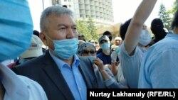 Председатель общественного совета Алматы Рахман Алшанов призывает разойтись людей, вышедших на мирный митинг. 6 июня 2020 года.