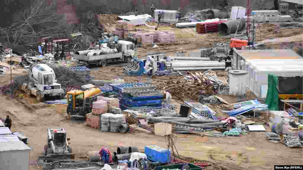 На площадке возле вагончиков все вперемешку: техника, стройматериалы и строительный мусор