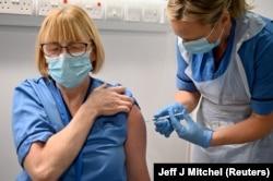 Британдык Грейс Томсон айым «Pfizer/BioNTech» вакцинасы менен өзүн эмдетти. Глазго, Шотландия. 2020-жылдын 8-декабры.