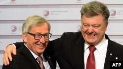 Ukrainian President Petro Poroshenko (right) is greeted by the president of the European Commission, Jean-Claude Juncker, in Riga.