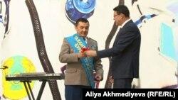 Казахстанскому космонавту Айдыну Аимбетову (слева) вручают регалии почетного жителя Талдыкоргана. 15 октября 2015 года.