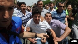 Plainclothes police officers detain opposition activists who tried to hold a rally near the public television station which is a partner for Eurovision broadcasts in Baku. (file photo)