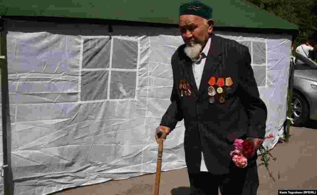 Ветеран рядом с палаткой, поставленной ко Дню Победы в Парке имени 28 гвардейцев-панфиловцев. Алматы, 9 мая 2013 года.