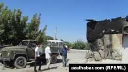 Местные жители показывают на поврежденный от взрыва дом в поселке близ Абадана. Туркменистан.