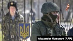 Российский военнослужащий без знаков отличия у военной базы Украины в Крыму в марте 2014 года