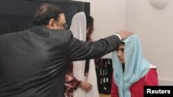 Pakistani President Asif Zardari greets Malala Yousafzai during his visit to the Queen Elizabeth Hospital in Birmingham on December 8.