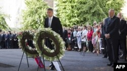 Norway's King Harald (right) and Norwegian Prime Minister Jens Stoltenberg (center) attend a wreath-laying ceremony at the site of a bomb attack that killed eight people in Oslo last year.