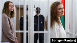 Katsyaryna Andreyeva (right) and Darya Chultsova stand inside the defendants' cage during the court hearing in Minsk on February 18.