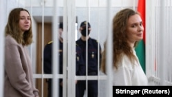BELARUS - Katsiaryna Andreyeva and Darya Chultsova, Belarusian journalists working for the Polish television channel Belsat accused of coordinating mass protests in 2020 by broadcasting live reports, stand inside a defendants' cage during a court hearing