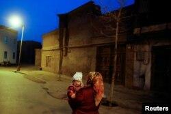 Женщина несет ребенка на руках в Кашгаре. Синьцзян, Китай, 23 марта 2017 года.