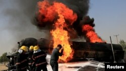 Afghan firefighters attempt to extinguish a burning fuel tanker which was hit by a magnetic bomb on the outskirts of Jalalabad