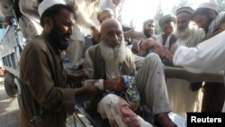 Men assist fellow Afghans injured in a bomb blast as they arrive at a hospital in Jalalabad in September.