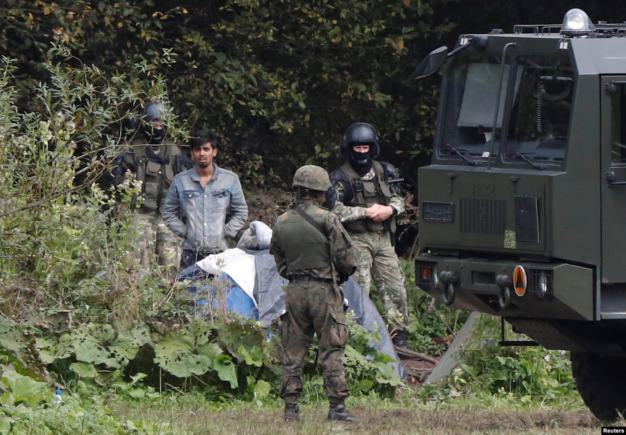 A migrant on the border with Belarus on August 23. The man is part of a group of migrants claiming to be from Afghanistan caught in a bizarre standoff between Polish and Belarusian border guards.
