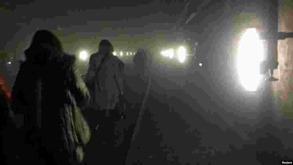 During the evacuation, passengers walk along the underground metro tracks.
