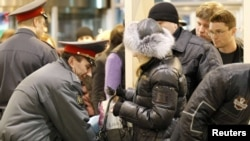 A police officer checks the hand baggage of a woman as people wait in a line to pass through a metal detector at Moscow's Domodedovo airport on January 25, less than 24 hours after the devastating bombing.