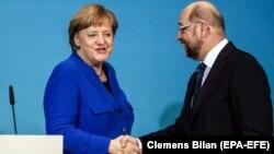 Германия канцлері Ангела Меркель (сол жақта) мен Социал-демократиялық партия жетекшісі Мартин Шульц қол алысып тұр. Берлин, 12 қаңтар 2018 жыл
