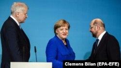 Прем'єр-міністр Баварії та глава Християнсько-соціального союзу Хорст Зігофер спотерігає за рукостисканням канцлера Анґели Меркель та лідера соціал-демократів Мартіна Шульца під час прес-конференції після чергового раунду коаліційних переговорів у січні 2018 року.