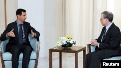 Syrian President Bashar al-Assad (left) meets with U.S. Ambassador Robert Ford in Damascus on January 27.