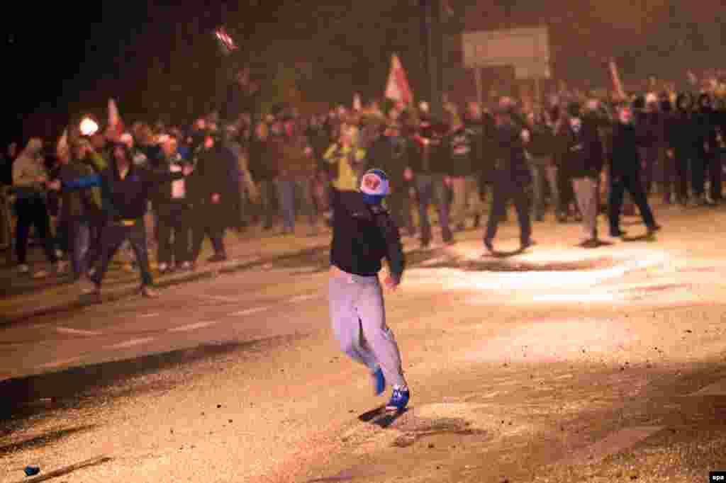 Один из участников акции бросает зажженный файер