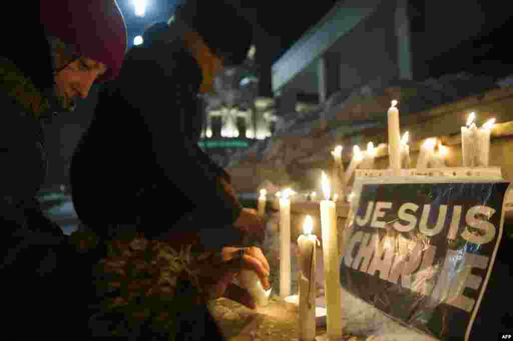 "An ethnic Albanian woman lights a candle next to a sign reading in French ""I Am Charlie"" during a gathering in Pristina, Kosovo, to remember the victims of the January 7 shootings at the offices of the French satirical magazine Charlie Hedbo. Twelve people died in the attack."