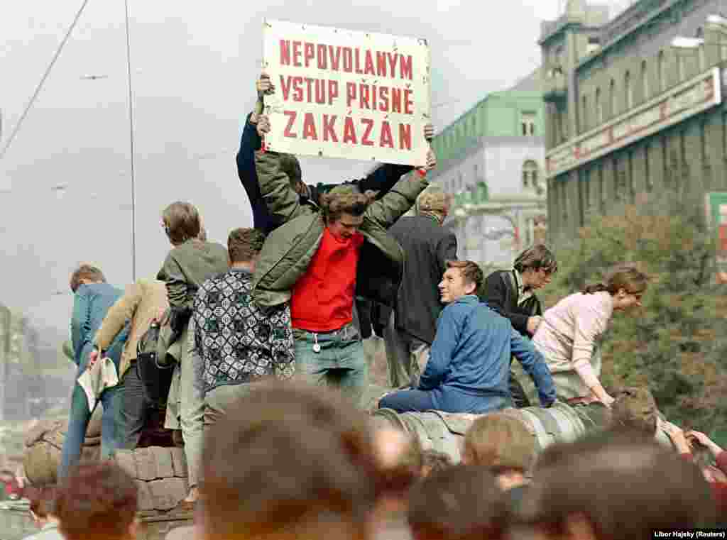 "The lighthearted atmosphere on the streets at this time is evident in the sign saying, ""Unauthorized Access Strictly Prohibited,"" which these young people had commandeered from a nearby building site. ""They rode on the tank employing this typical dark Czech humor,"" Hajsky says. ""People were smiling. At that moment, they still saw it as some sort of spectacle.... But then, of course, things began to go in a different direction..."""