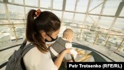 Женщина и ребенок у отпечатка ладони бывшего президента Нурсултана Назарбаева в стеклянной сфере на вершине монумента «Байтерек». Нур-Султан, 16 ноября 2020 года.