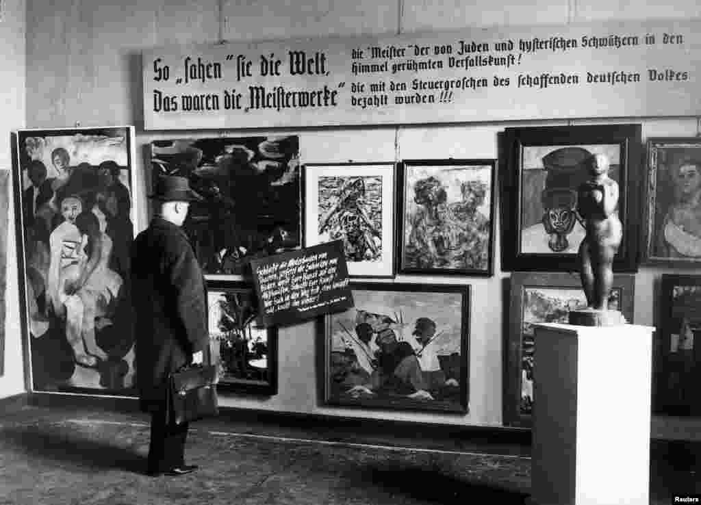 "A man looks at pieces from the Nazi-curated travelling exhibition, ""Degenerate Art"" (""Entartete Kunst""), which was displayed at the Haus der Kunst in Berlin on February 24, 1938."