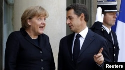 French President Nicolas Sarkozy (right) welcomes German Chancellor Angela Merkel prior to a working lunch at the Elysee Palace in Paris last month.
