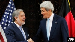 Presidential candidate Abdullah Abdullah (left) shakes hands with U.S. Secretary of State John Kerry in Kabul on July 11, 2014.