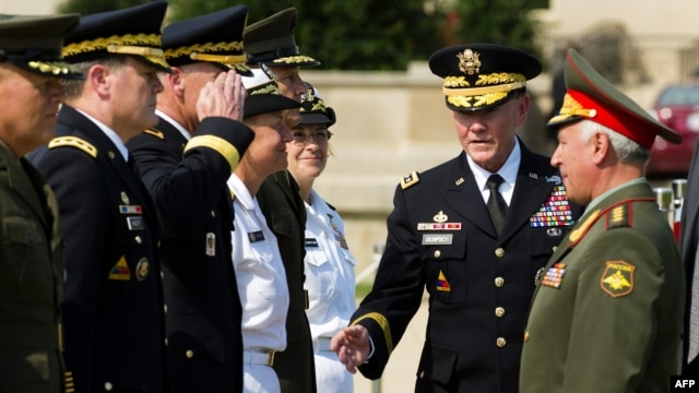 Russian General of the Army Nikolai Makarov (right) is introduced by U.S. Chief of Staff General Patrick Dempsey (center) during a full honor cordon at the Pentagon in Washington on July 12.