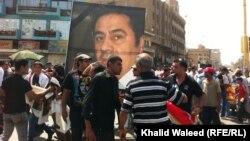 متظاهرون في بغداد يحملون صورة لهادي المهدي العام الماضي