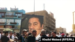 Protesters on Baghdad's Freedom Square rally against corruption and the poor state of public utilities while carrying photos of Iraqi civil activist Hadi al-Mehdi, who had co-organized a number of regular Friday antigovernment protests until he was murder