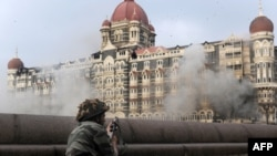 An Indian soldier aims his weapon toward the Taj Mahal Hotel during the military operation against militants in Mumbai.